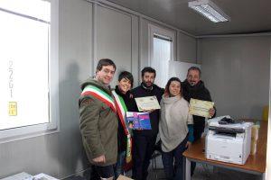 Serena Olivieri, Sara Corelli e Gabriele Giampietri, consegnano agli amministratori locali una stampante, risme e 12 tablet per le scuole locali