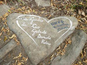 Un sasso a forma di cuore con una scritta a ricordo di Giulio Armanini