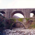 L'antico ponte sul Magriola a Mignegno dominato dal più recente manufatto su cui transita la strada statale.