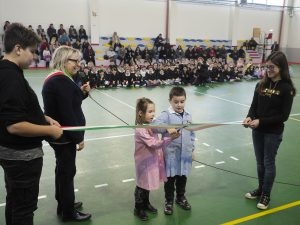 Il taglio del nastro della nuova palestra da parte di due giovani alunni sotto l'occhio vigile del sindaco Annalisa Folloni (foto Massimo Pasquali)