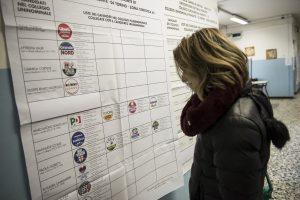 Un'elettrice davanti all'elenco dei partiti e dei candidati