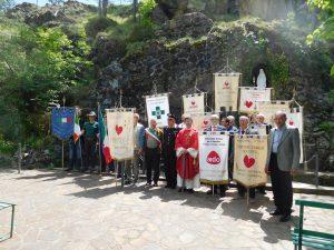 Un momento della giornata della Festa Fratres a Zeri con i labari delle varie associazioni presenti davanti alla Grotta di Lourdes