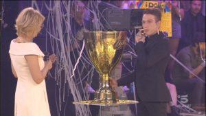 """Irama ottiene il trofeo simbolo della vittoria di """"Amici"""" dalle mani della conduttrice Maria De Filippi"""