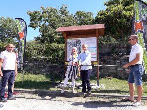 La sindaca Annalisa Folloni e l'onorevole Cosimo Maria Ferri tagliano il nastro davanti alla tabella che illustra i sentieri