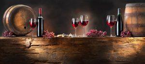Bicchieri di vino rosso con botti e trave