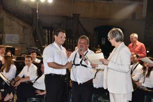 La sindaca Lucia Baracchini e il presidente della Musica Cittadina Elio Poli, consegnano l'attestato al nuovo musicante Geminiano Bertocchi (tromba)