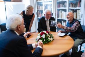 Il sopravvissuto Andrea Quartieri mostra una foto dei famigliari uccisi nell'eccidio del 1944 ai due presidenti.