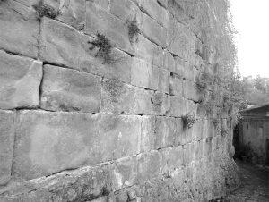 Il muro medievale dell'antica chiesa, caratterizzato da grosse bozze di arenaria